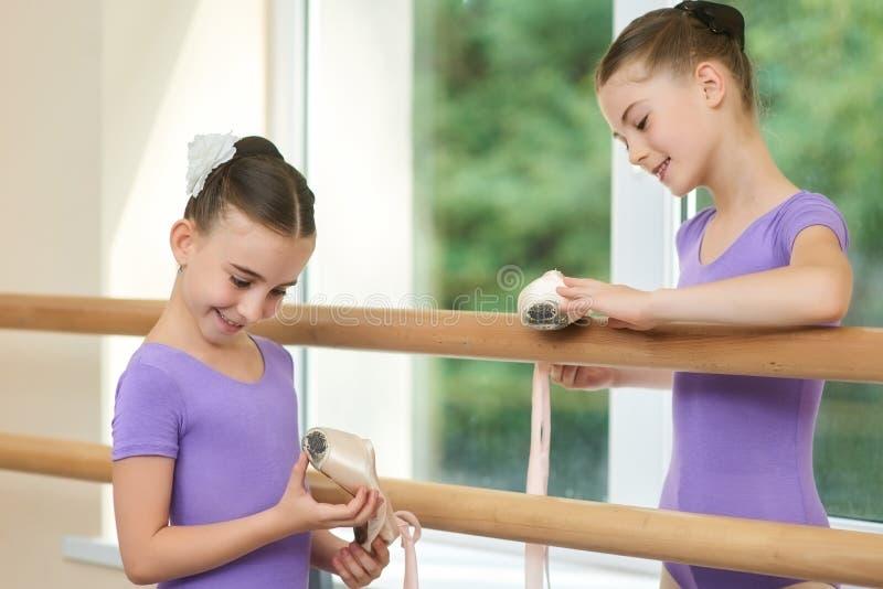 Счастливые маленькие балерины держа ботинки балета стоковые фото
