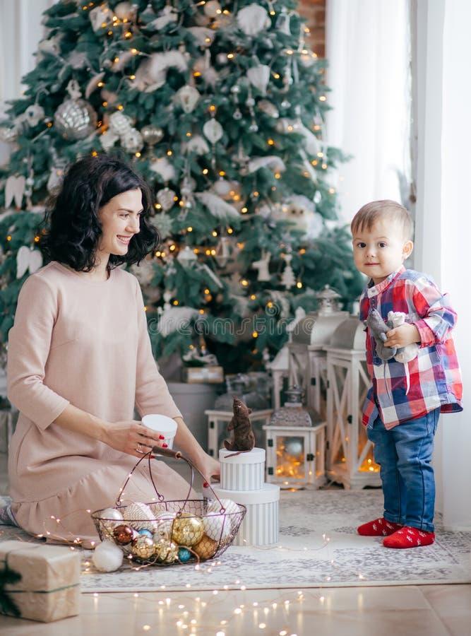 Счастливые маленькие ребенок и мать около рождественской елки стоковая фотография
