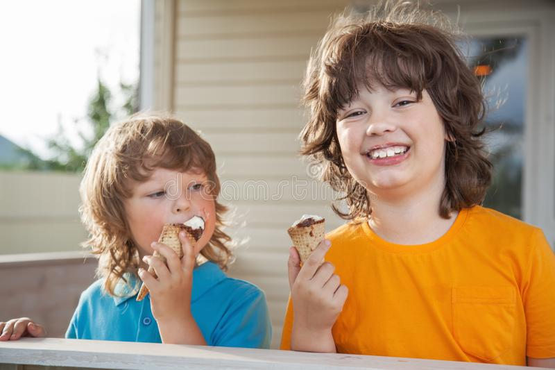 Счастливые мальчики есть мороженое стоковое изображение