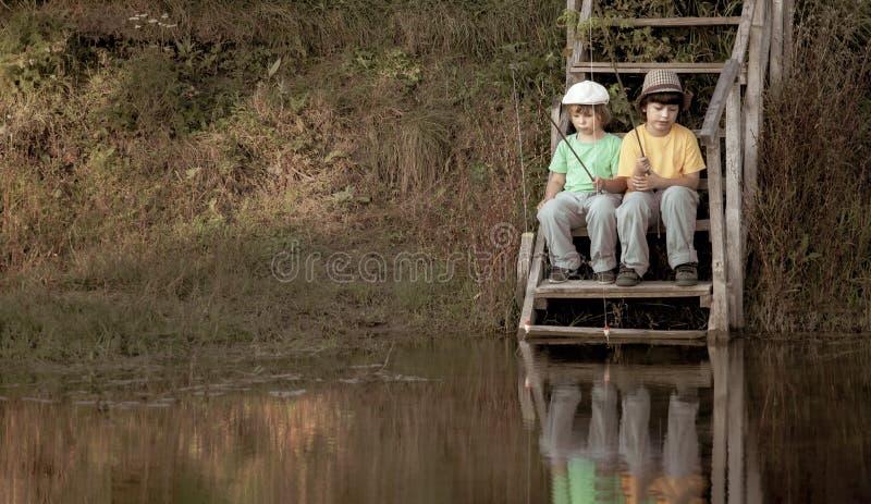 Счастливые мальчики идут удить на реке, 2 детях рыболова с рыболовной удочкой на береге озера стоковые изображения rf