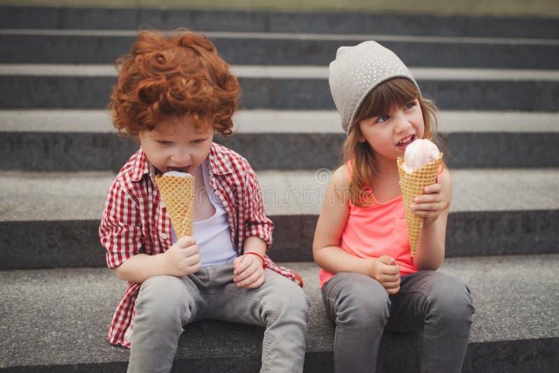 Счастливые мальчик и девушка с мороженым стоковая фотография rf