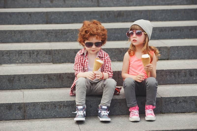Счастливые мальчик и девушка с мороженым стоковые фотографии rf