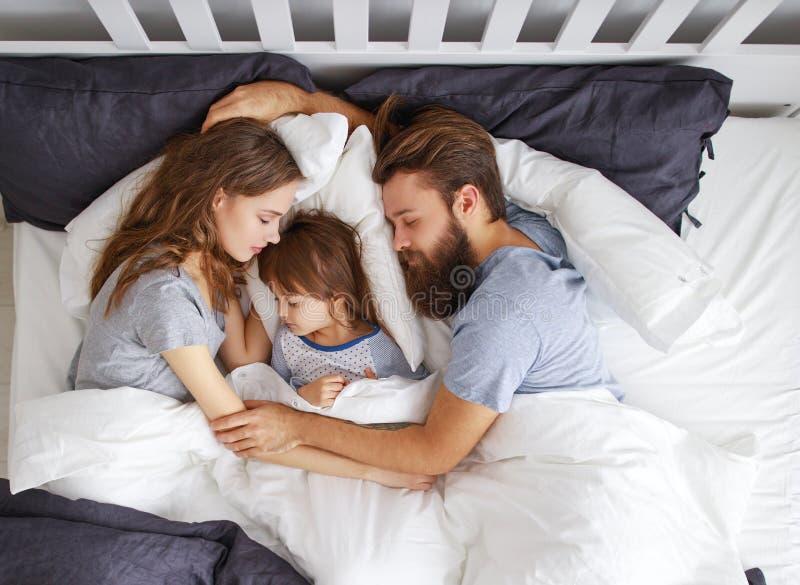 Счастливые мать, отец и ребенок семьи спать в кровати стоковое фото rf