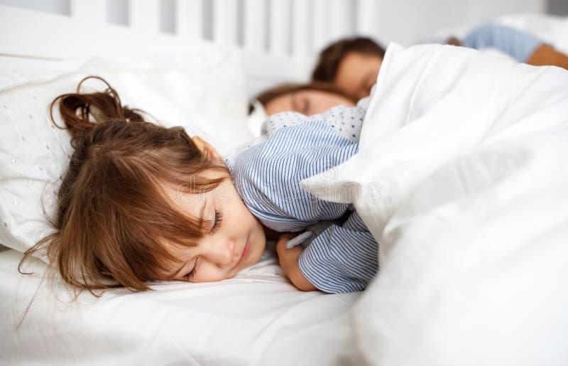 Счастливые мать, отец и ребенок семьи спать в кровати стоковое фото
