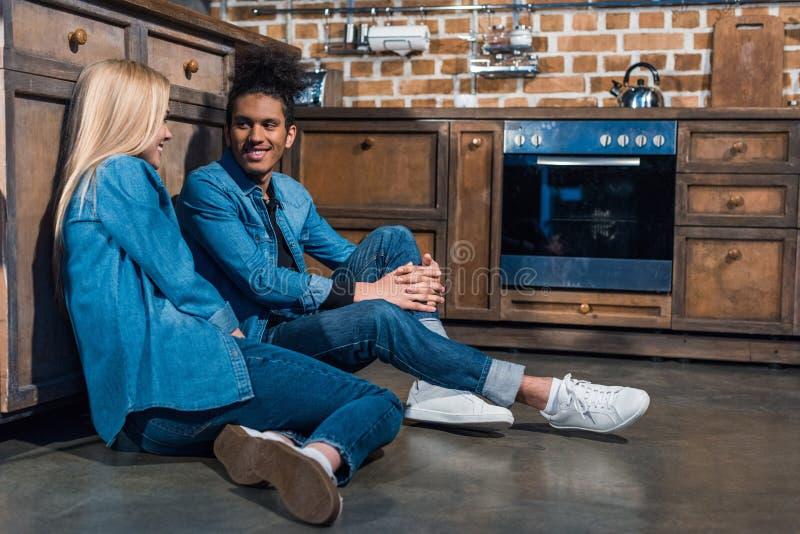 счастливые межрасовые пары сидя на поле в кухне стоковые изображения
