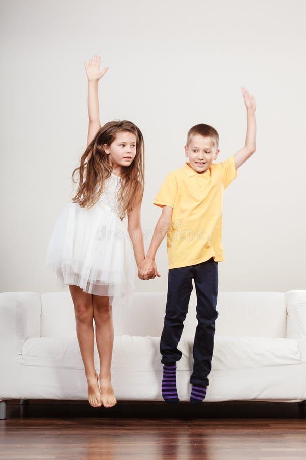 Счастливые милые дети маленькая девочка и скакать мальчика стоковое фото rf