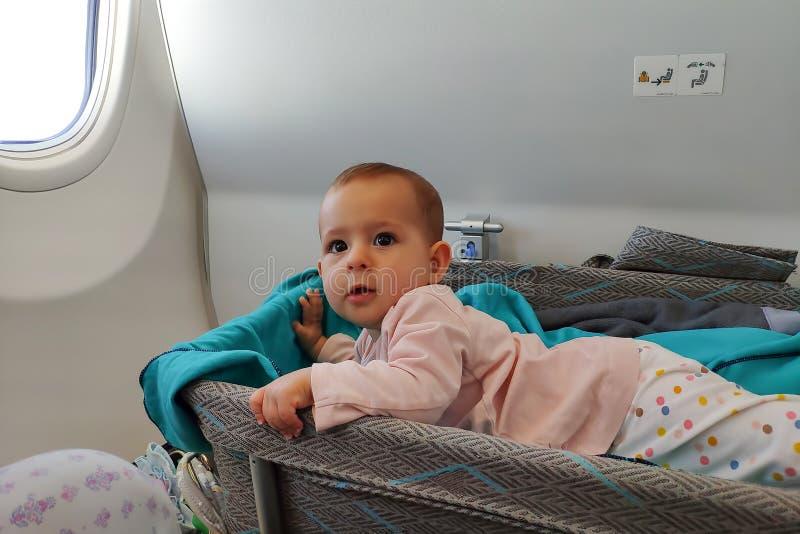 Счастливые младенческие отзолы младенца в особенном bassinet в самолете на его животе Первый полет младенца, она впечатлена Путеш стоковые фото