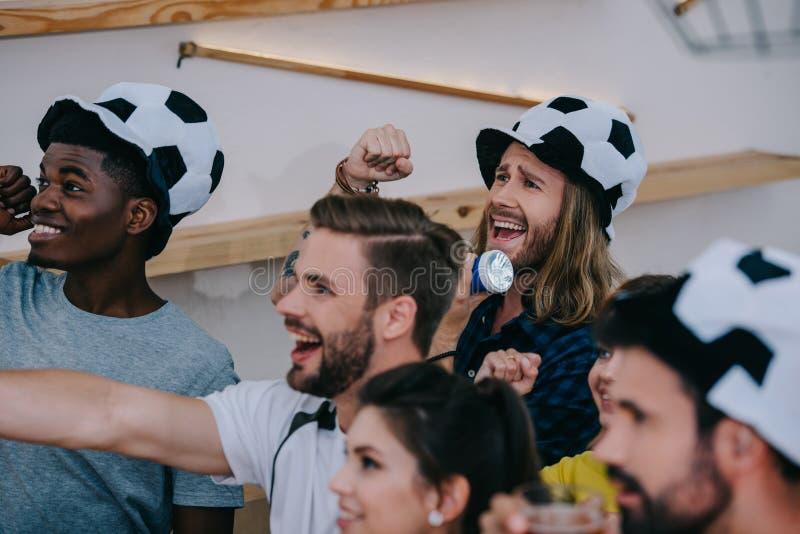 счастливые многокультурные друзья в шляпах футбольного мяча празднуя показывать жестами руками и наблюдая футбольный матч стоковые фото