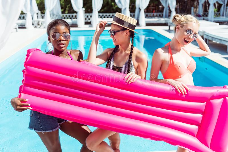 Счастливые многонациональные женщины представляя с раздувным тюфяком около бассейна стоковые фотографии rf