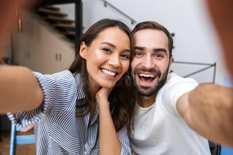 Счастливые многонациональные пары имея завтрак стоковые фотографии rf
