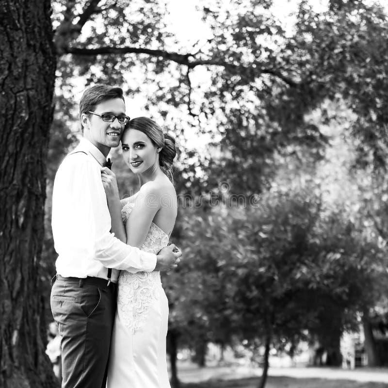 Счастливые молодожены, стоящие возле городского озера черно-белая фотография стоковое фото rf