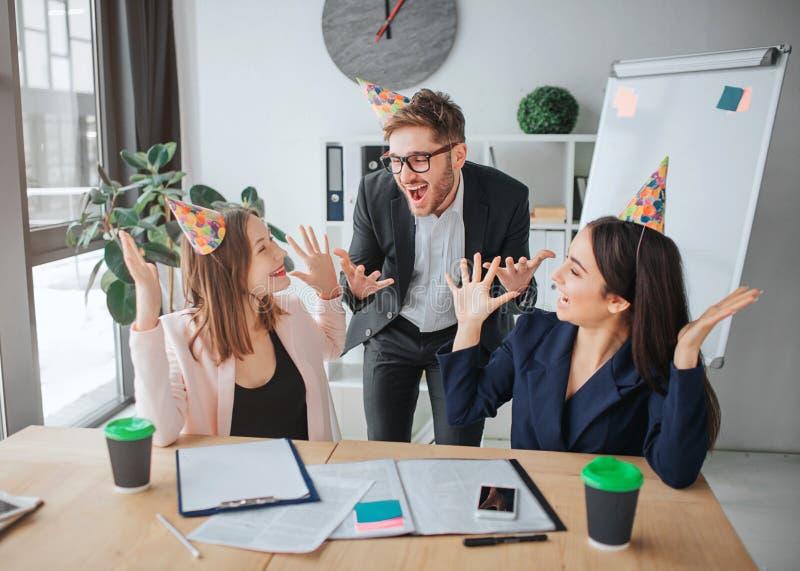 Счастливые молодой человек и женщины на таблице в праздновать конференц-зала Они клекот и иметь потеху Люди носят b-дневные шляпы стоковая фотография rf