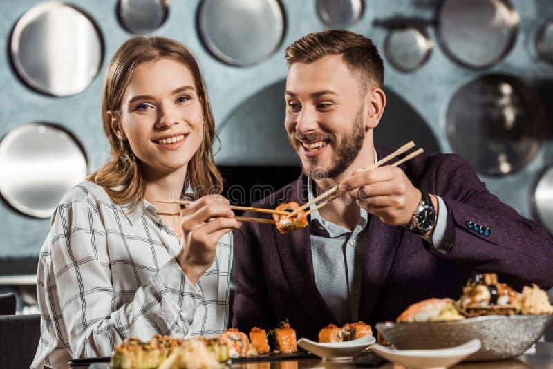 Счастливые молодые взрослые пары есть суши стоковое изображение