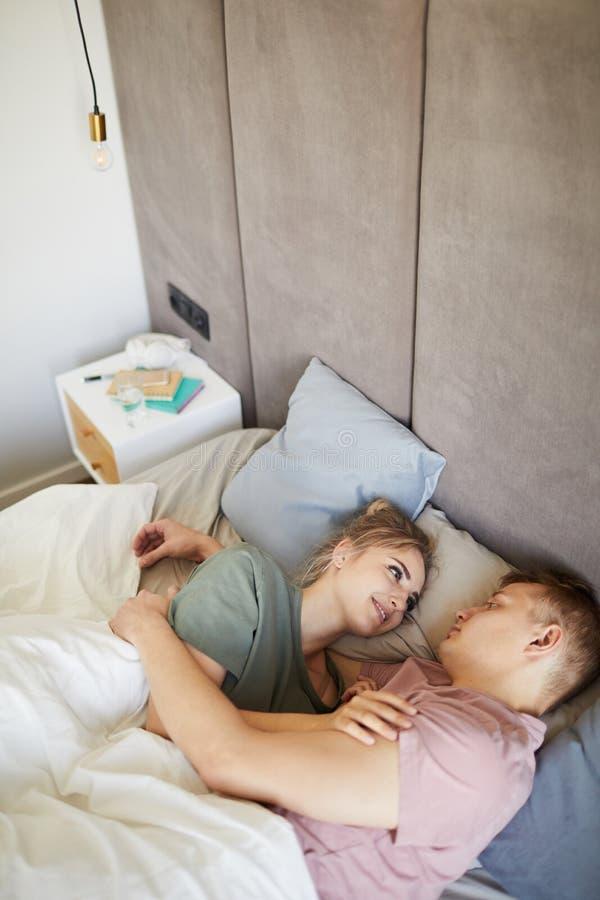 Счастливые молодые влюбчивые супруги смотря одно другое в кровати стоковая фотография rf