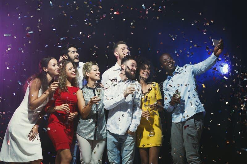 Счастливые молодые друзья имея партию на ночном клубе и teking selfie стоковое изображение rf