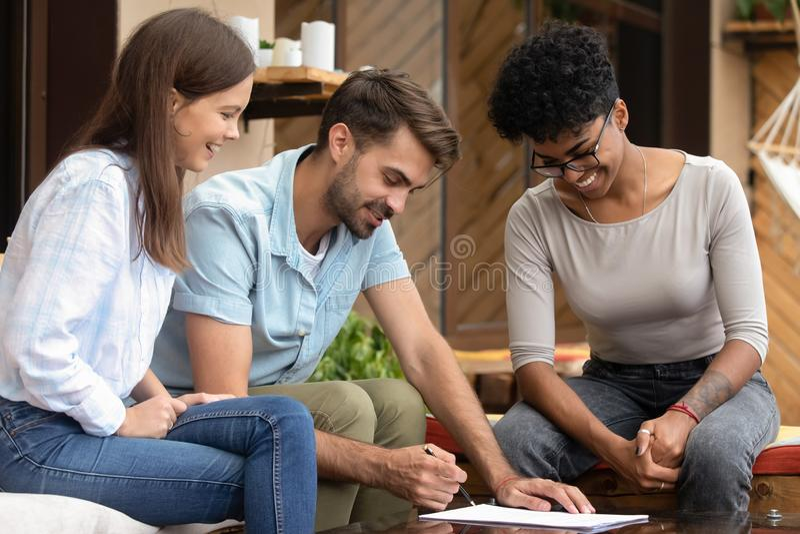 Счастливые молодые клиенты пар семьи подписывают страховщика встречи контракта ипотеки стоковые фото