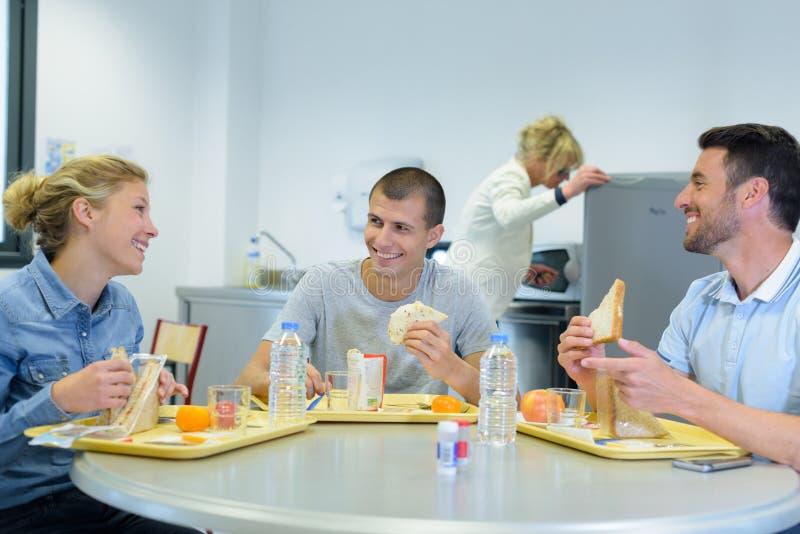 Счастливые молодые коллеги имея обед стоковые фотографии rf