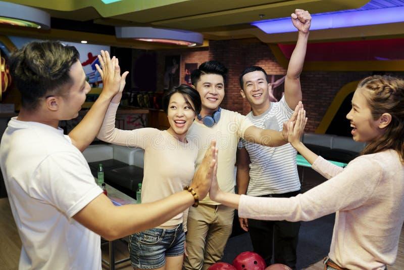 Счастливые молодые люди в клубе боулинга стоковая фотография rf