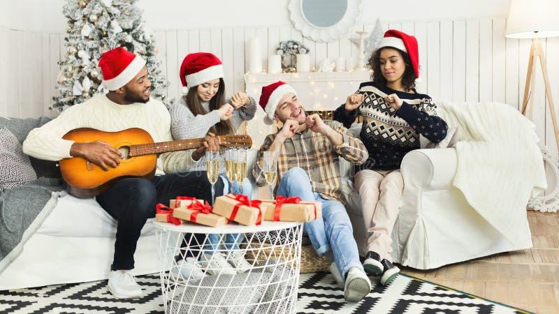 Счастливые молодые люди празднуя рождество дома стоковое изображение