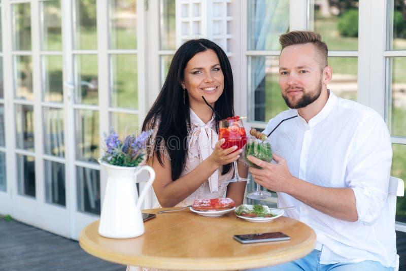 Счастливые молодые люди сидят в кафе, показали очень вкусные коктейли ягоды, беседующ, тратя время совместно Человек внутри стоковые изображения