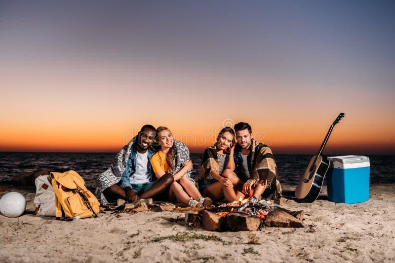 счастливые молодые люди усмехаясь на камере пока сидящ совместно на песчаном пляже стоковое изображение rf