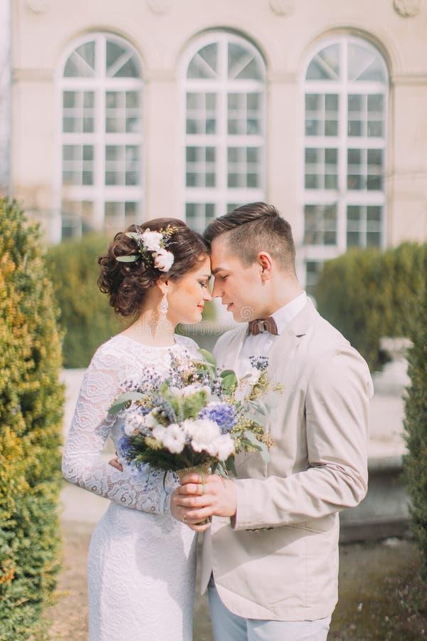 Счастливые молодые новобрачные обнимая около старого бежевого дома с столбцами и большими винтажными окнами Романтичная свадьба в стоковые изображения