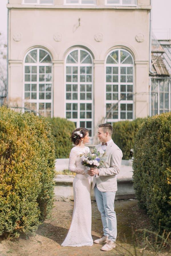 Счастливые молодые новобрачные обнимая около старого бежевого дома с столбцами и большими винтажными окнами Романтичная свадьба в стоковая фотография rf