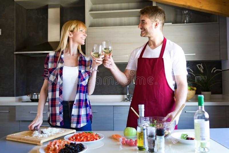 Счастливые молодые пары варя совместно и провозглашать с стеклами вина в кухне стоковое фото