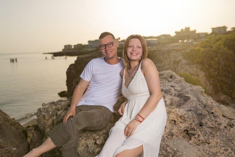 Счастливые молодые пары в любов усмехаясь морем стоковые изображения