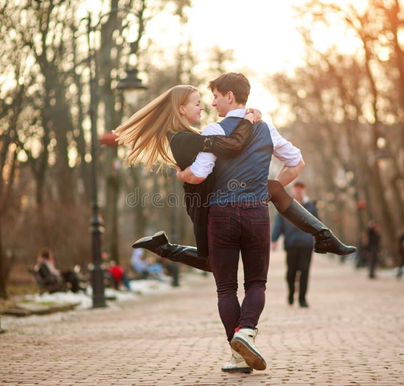 Счастливые молодые пары в новобрачных любов joyfully имея потеху в парке города стоковое фото