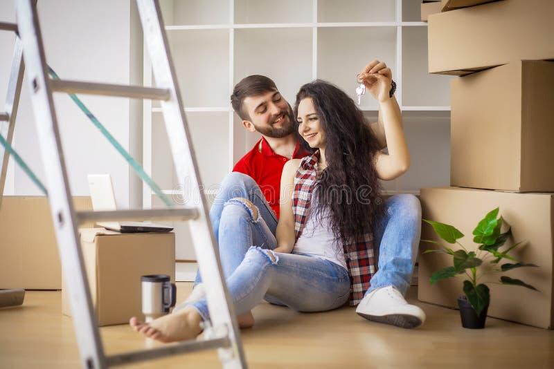 Счастливые молодые пары двигая в новый дом распаковывая коробки стоковые фотографии rf