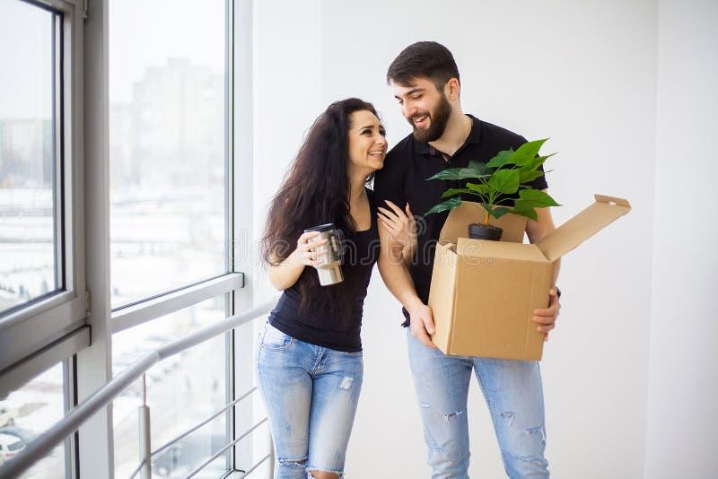 Счастливые молодые пары двигая в новый дом распаковывая коробки стоковые изображения