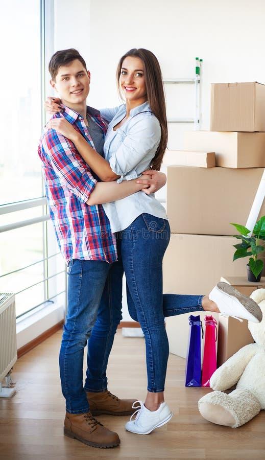 Счастливые молодые пары двигая совместно в новую квартиру стоковое фото
