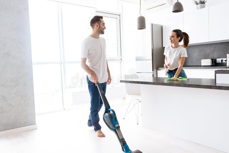 Счастливые молодые пары делая генерала чистый на кухне стоковые изображения