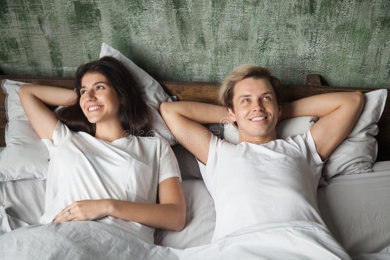 Счастливые молодые пары мечтая лежать в кровати в утре стоковые изображения