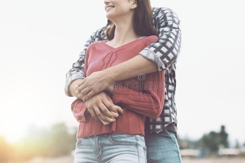 Счастливые молодые пары обнимая и усмехаясь стоковое изображение rf