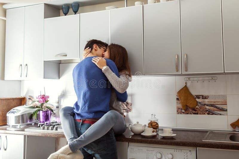 Счастливые молодые пары обнимая на кухне Женщина сидя на таблице стоковые фотографии rf