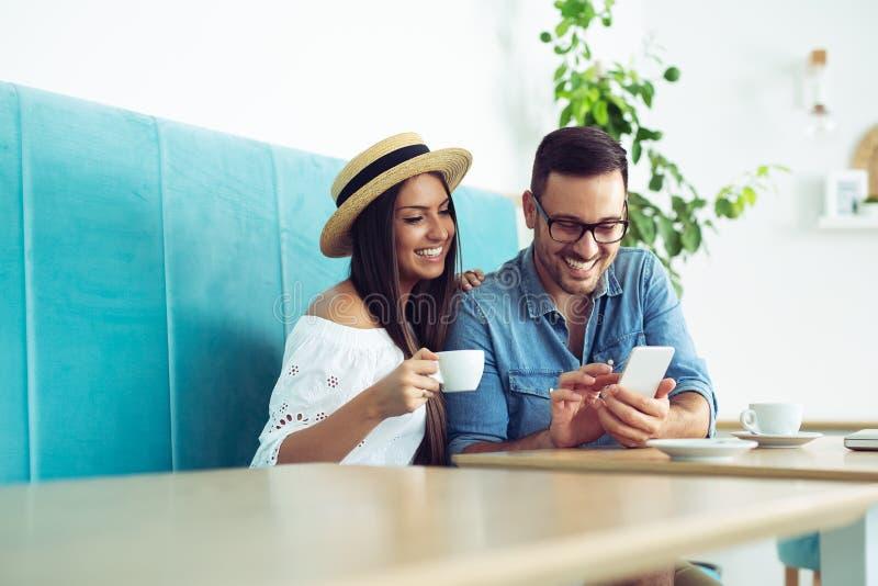 Счастливые молодые пары сидя на кафе ставят выпивая кофе и смотреть на обсуждение мобильный телефон стоковое фото rf