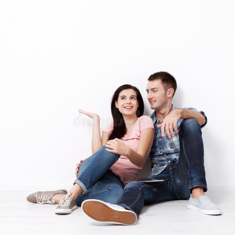 Счастливые молодые пары сидя на поле смотря вверх пока мечтающ их новые домашнее и обеспечение Насмешка вверх стоковое изображение