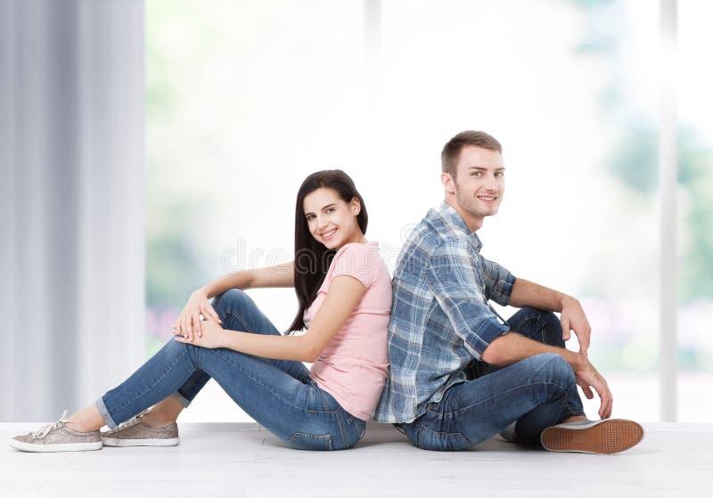 Счастливые молодые пары сидя на поле смотря вверх пока мечтающ их новые домашнее и обеспечение Насмешка вверх стоковые изображения