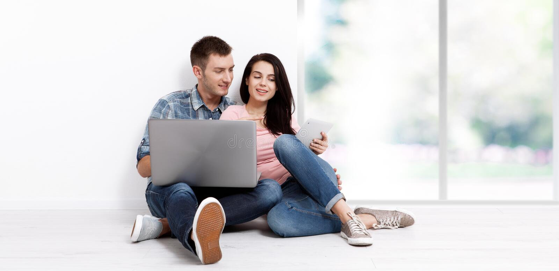 Счастливые молодые пары сидя на поле с ноутбуком ища их новые дом и мебель Насмешка вверх стоковые изображения rf