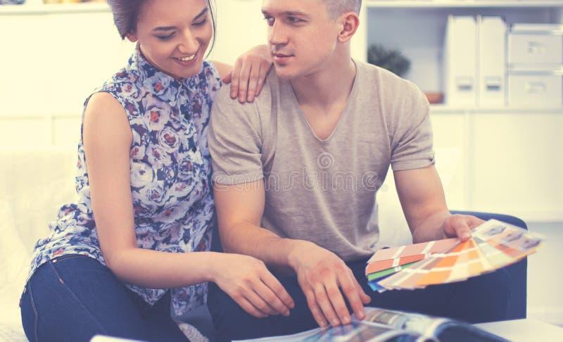 Счастливые молодые пары сидя совместно на софе стоковое изображение rf