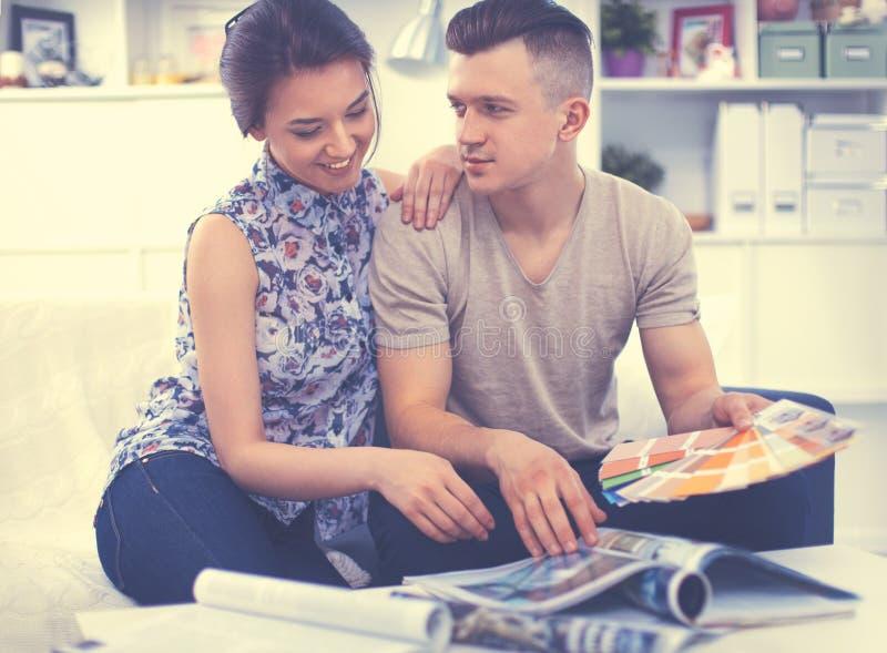 Счастливые молодые пары сидя совместно на софе стоковая фотография