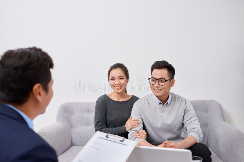 Счастливые молодые пары слушая мужской агент стоковое фото