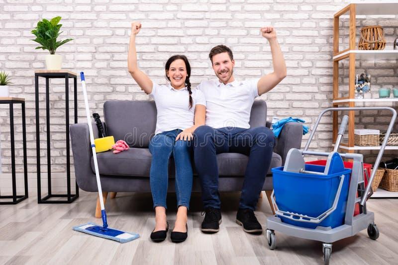Счастливые молодые пары со сжатым кулаком сидя на софе стоковое изображение