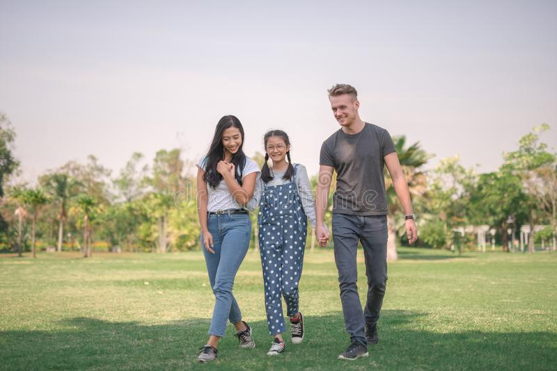 Счастливые молодые пары тратя время с их дочерью в парке Концепция счастливой семьи стоковое фото