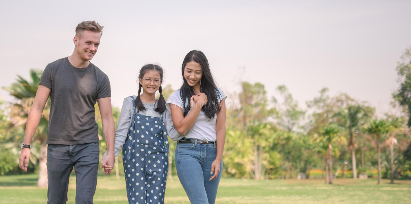 Счастливые молодые пары тратя время с их дочерью в парке Концепция счастливой семьи стоковая фотография rf