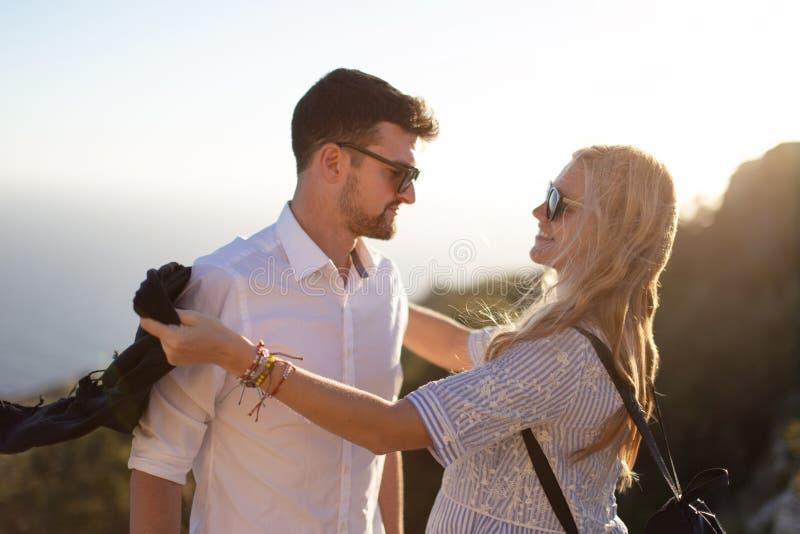 Счастливые молодые пары усмехаясь в заходе солнца совместно стоковые изображения