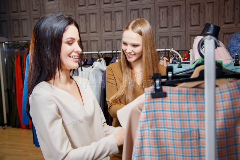 Счастливые молодые подруги выбирая новую одежду в магазине и усмехаться стоковое фото
