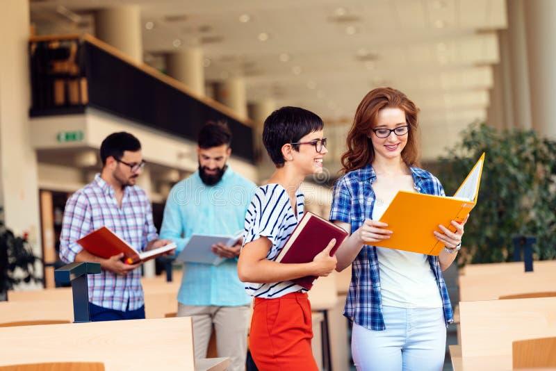 Счастливые молодые студенты университета изучая с книгами в библиотеке стоковое изображение
